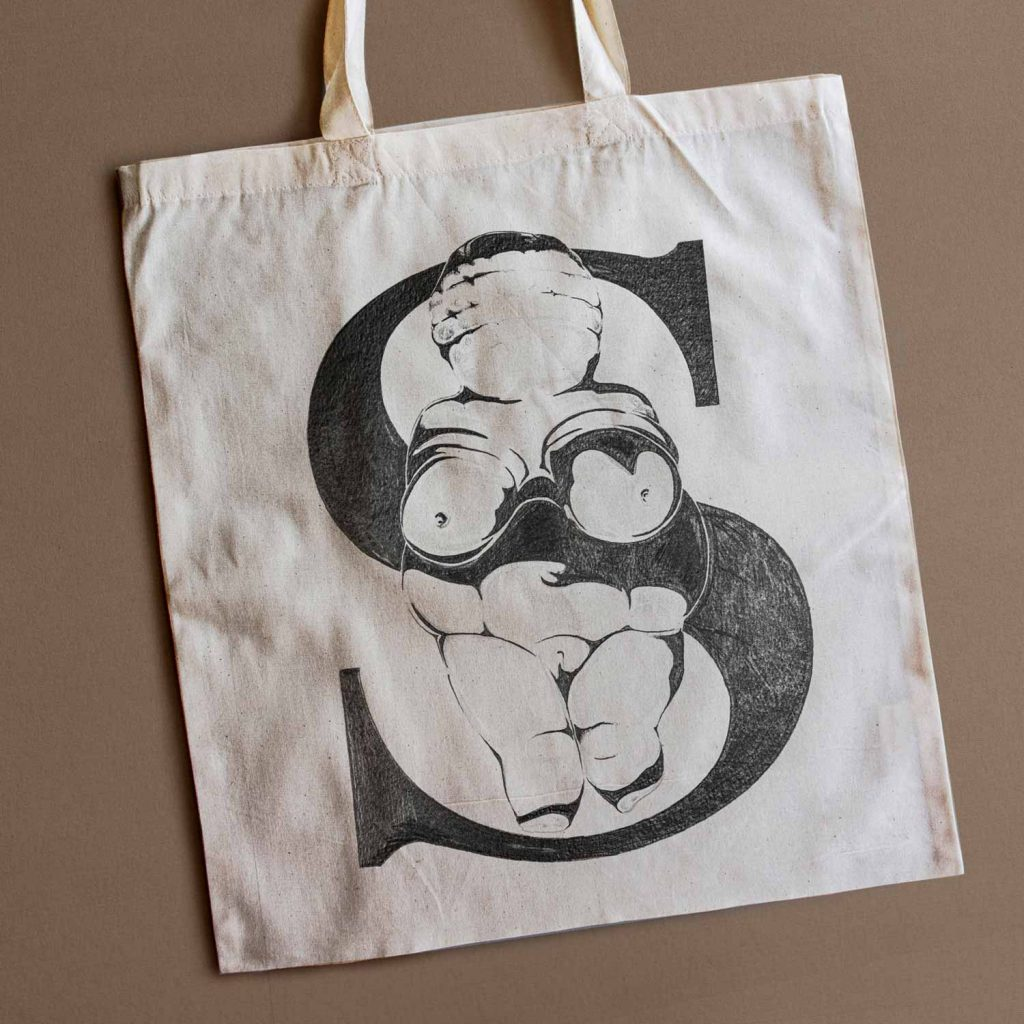 Tote bag with illustration of Venus of Willendorf and the S character written in Okaasan Serif